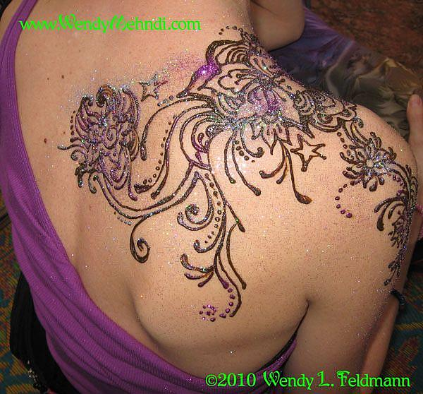 Henna design wrapping over a shoulder
