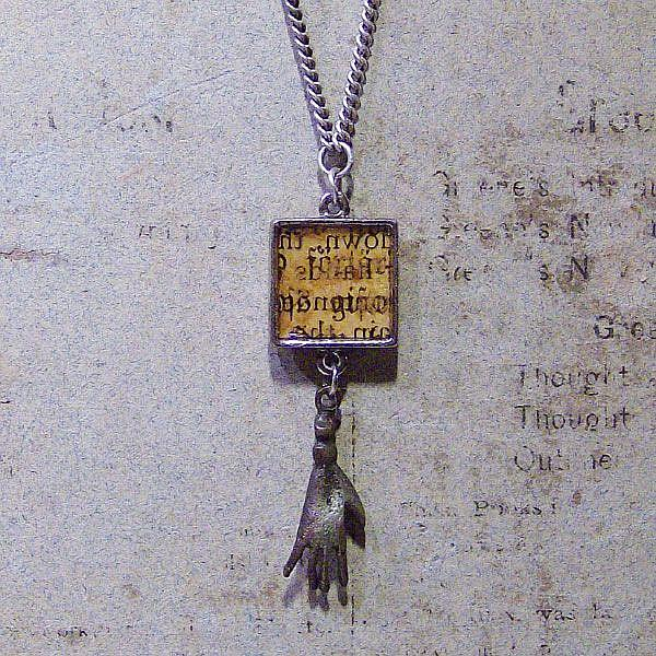 Art: Manuscript Milagro (hand) charm necklace by Artist Aria Nadii